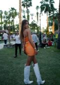 Lorena Rae rocks an orange mini dress with knee high white boots at Coachella in Indio, California
