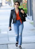 Lucy Hale wears a black leather jacket with a red top and jeans to run errands in West Hollywood, Los Angeles