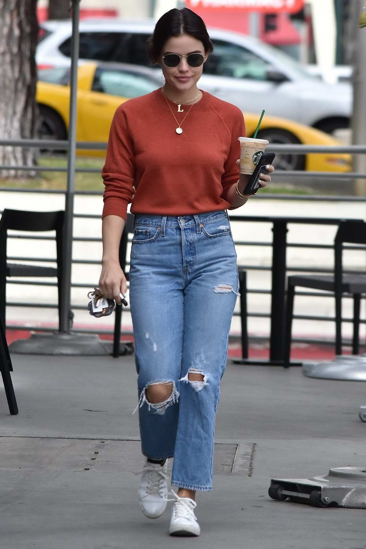 Lucy Hale wears an orange top and ripped jeans during a coffee run at Starbucks in Studio City, Los Angeles