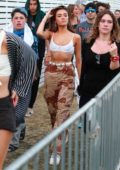 Madison Beer rocks camo pants and white bralette top while out with friends at Coachella in Indio, California