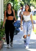 Madison Beer wears a white corset top and ripped jeans while out for a stroll with a friend in West Hollywood, Los Angeles