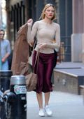 Martha Hunt is all smiles while carrying a garment bag as she arrives at Taylor Swift's apartment in New York City
