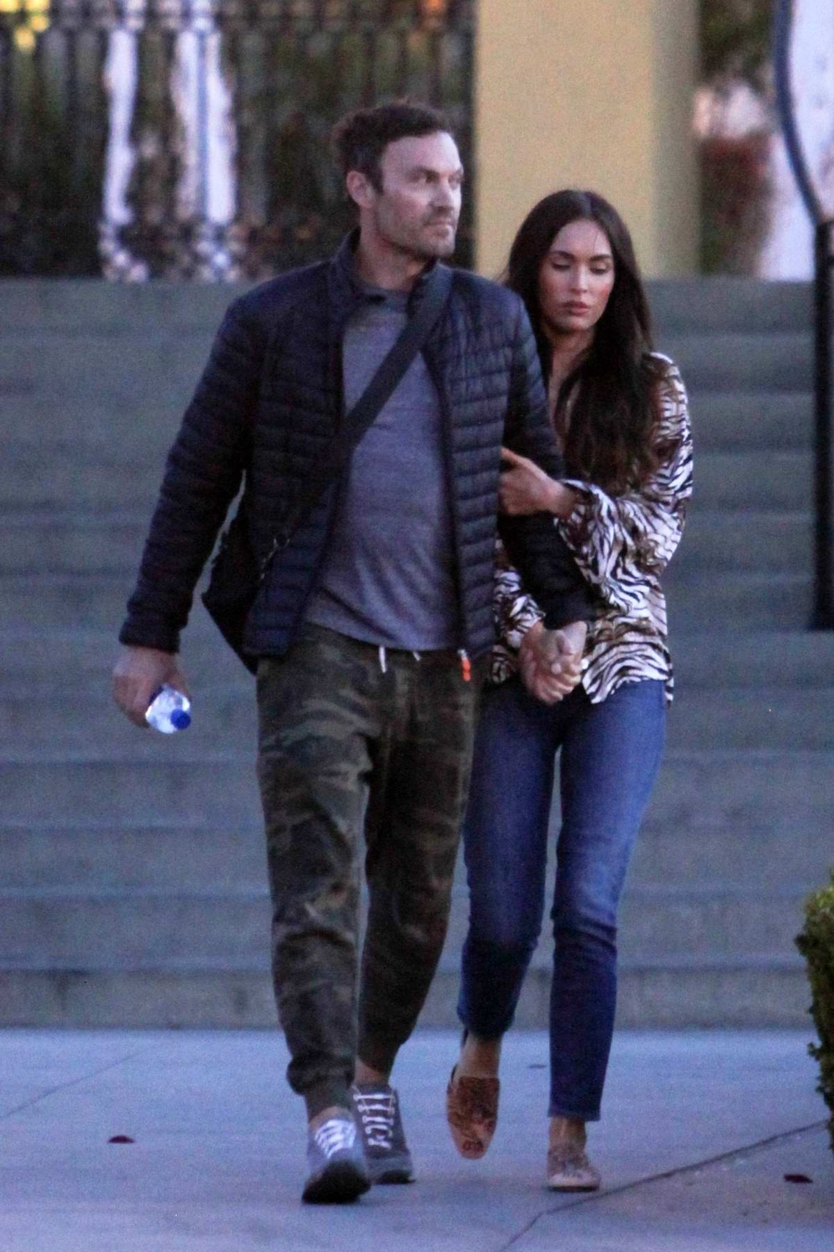 Megan Fox hold hands with Brian Austin Green hugging his arm while on a romantic date night in Los Angeles