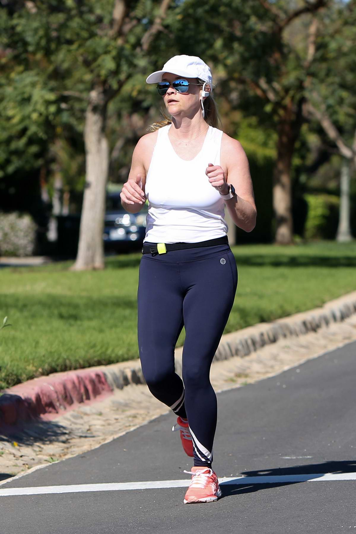 Reese Witherspoon out for her morning jog wearing a white tank top and black leggings in Los Angeles