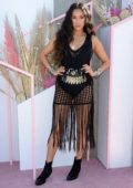 Shay Mitchell sports a net cover-up over a black swimsuit at the Revolve Festival during Coachella in Indio, California