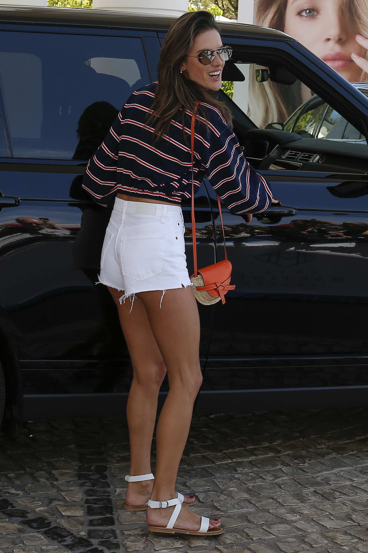 Alessandra Ambrosio rocks white denim shorts and striped top as she leaves her hotel in Cannes, France