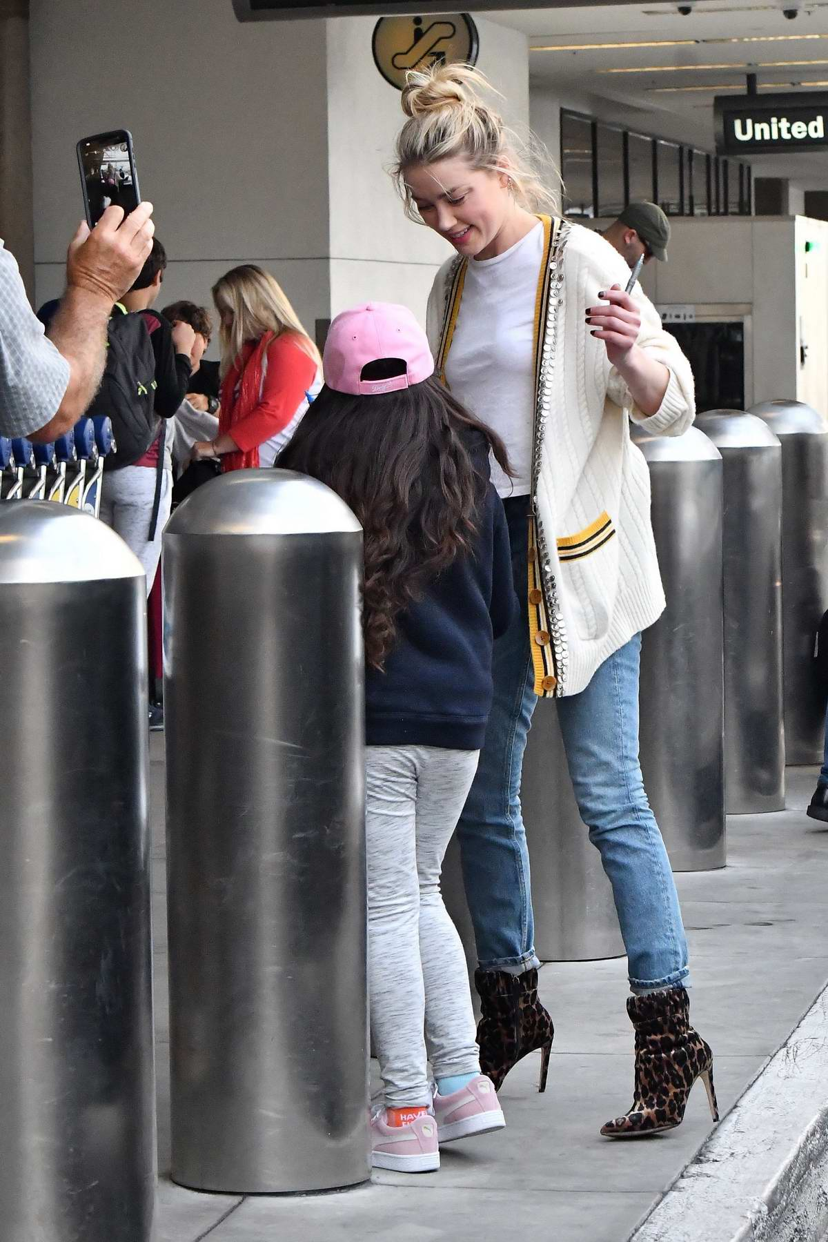 Amber Heard greets her fans as she touches down at LAX in Los Angeles