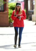 Ashley Benson wears a bright red sweatshirt and blue leggings as she leaves they gym in Studio City, Los Angeles