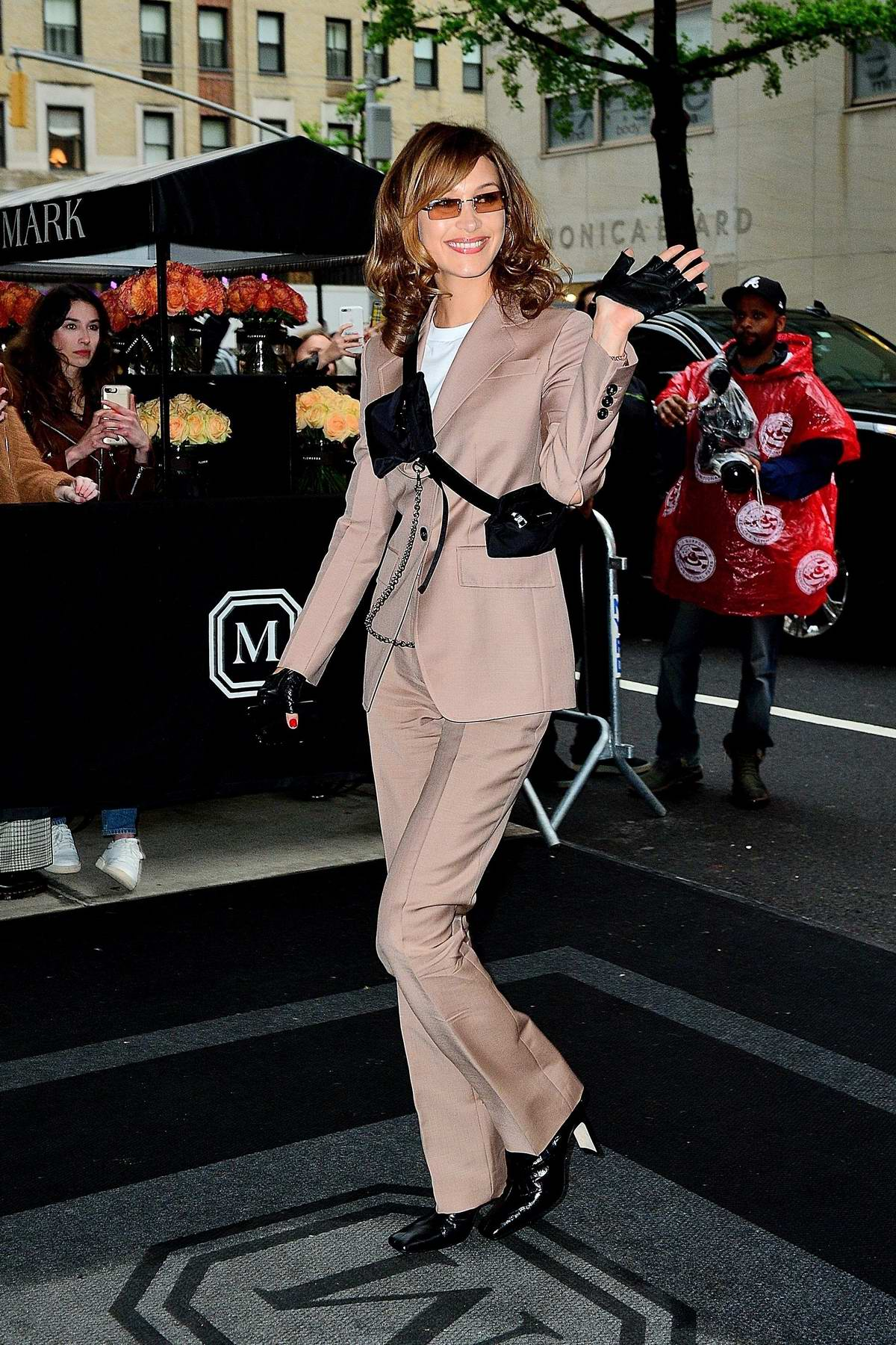 Bella Hadid looks fantastic in a dusty pink suit as she greet her fans while arriving at The Mark in New York City