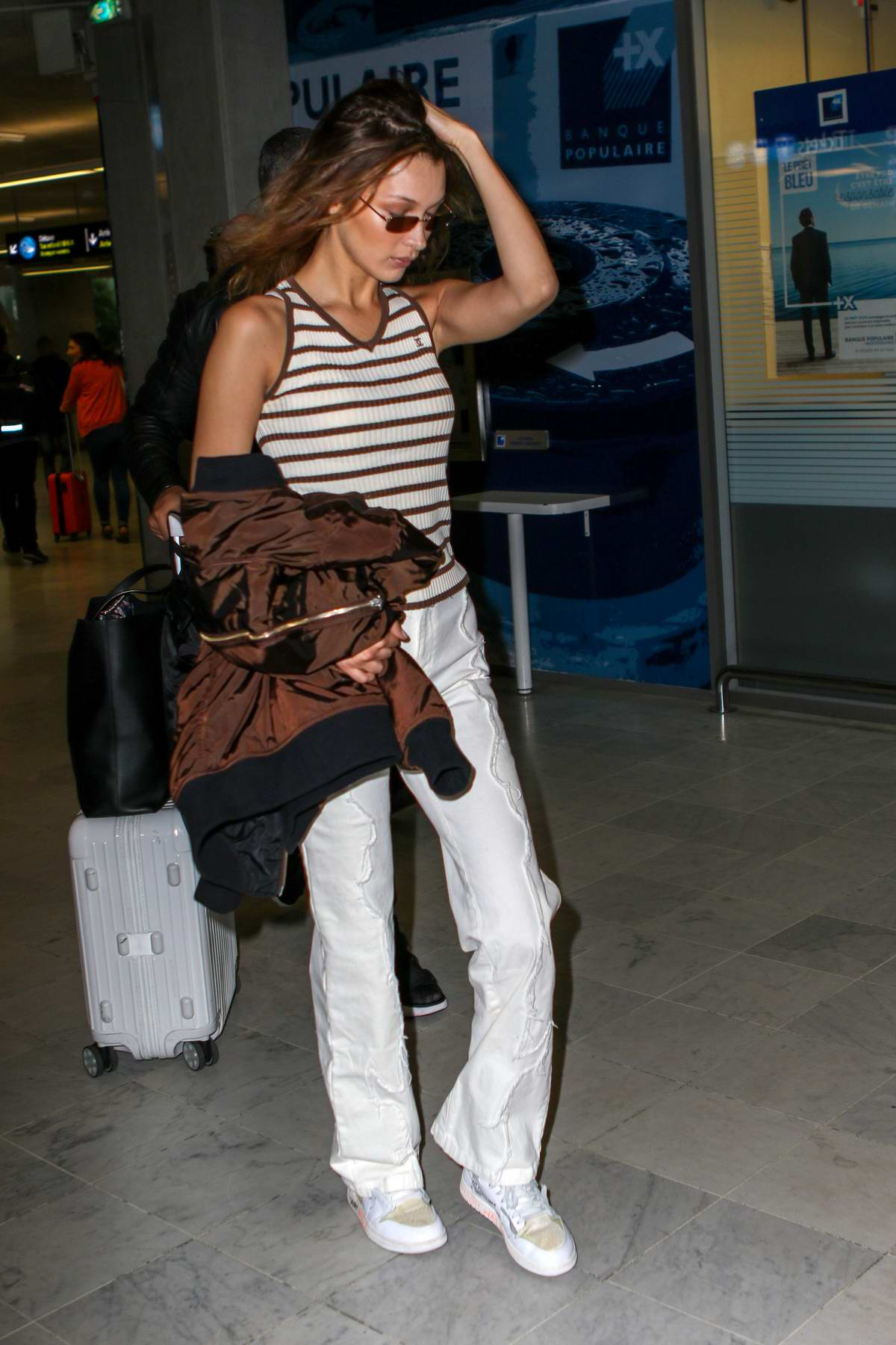 Bella Hadid spotted in a striped tank top and white pants as she arrives at Nice airport, France