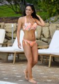 Casey Batchelor sports a floral print orange bikini while chilling by the pool in Tenerife, Spain