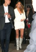 Chrissy Teigen flaunts her legs in a short white dress as she steps out in New York City