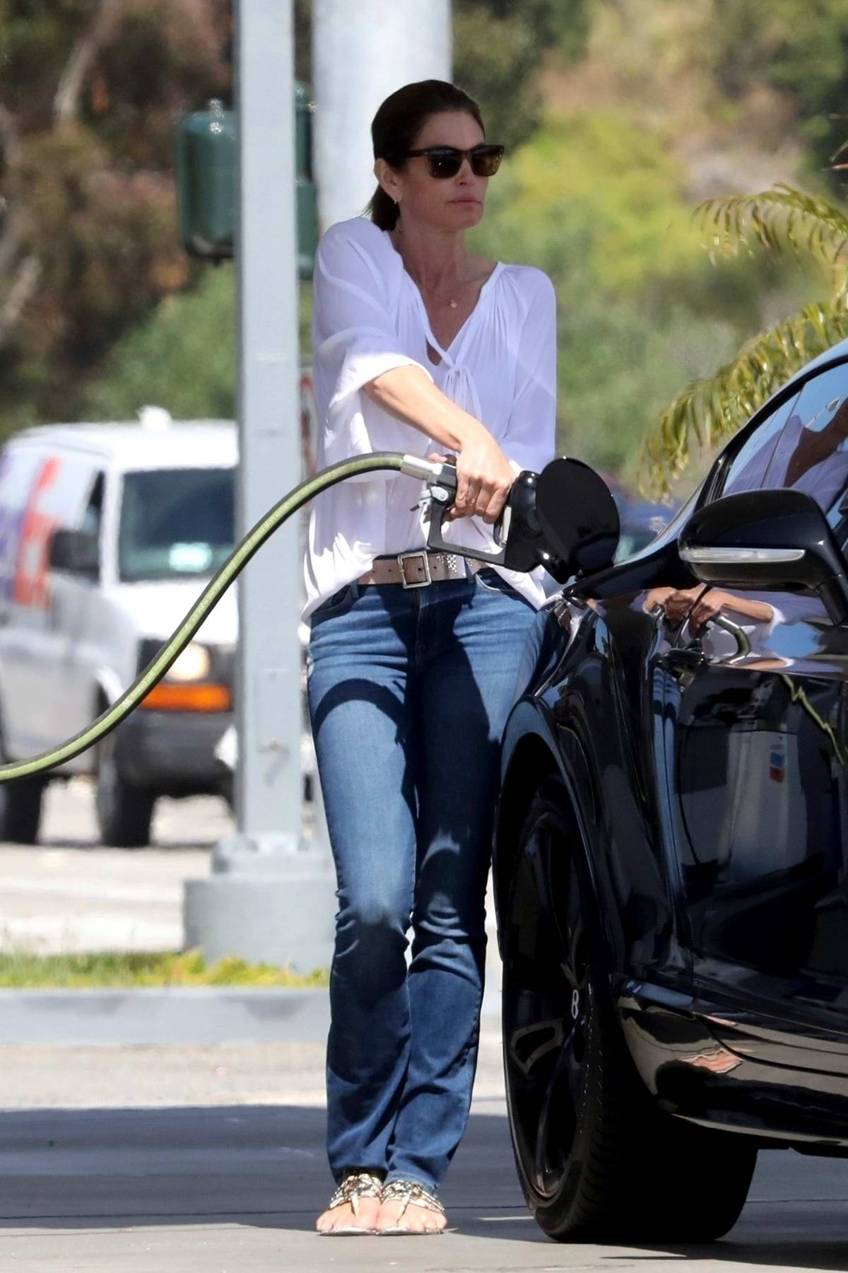 Cindy Crawford spotted in a white blouse and blue jeans as she stops by at a gas station to fill her car in Malibu, California