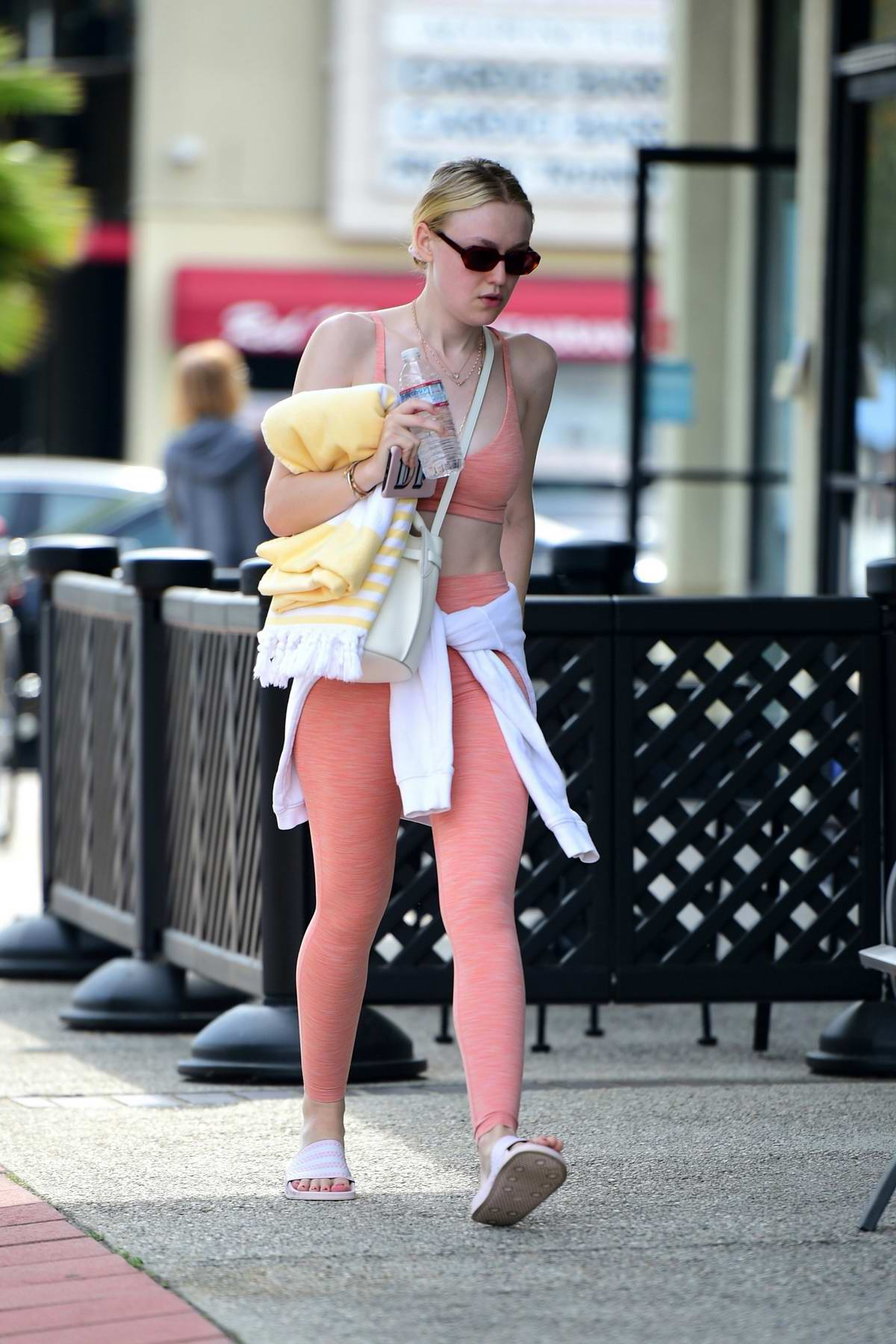 Dakota Fanning sports a peach colored crop top with matching leggings as she arrives for a workout at the gym in Studio City, Los Angeles