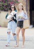 Dakota Johnson carries her dog while out for some iced coffee and drinks with Apple Martin in Malibu, California
