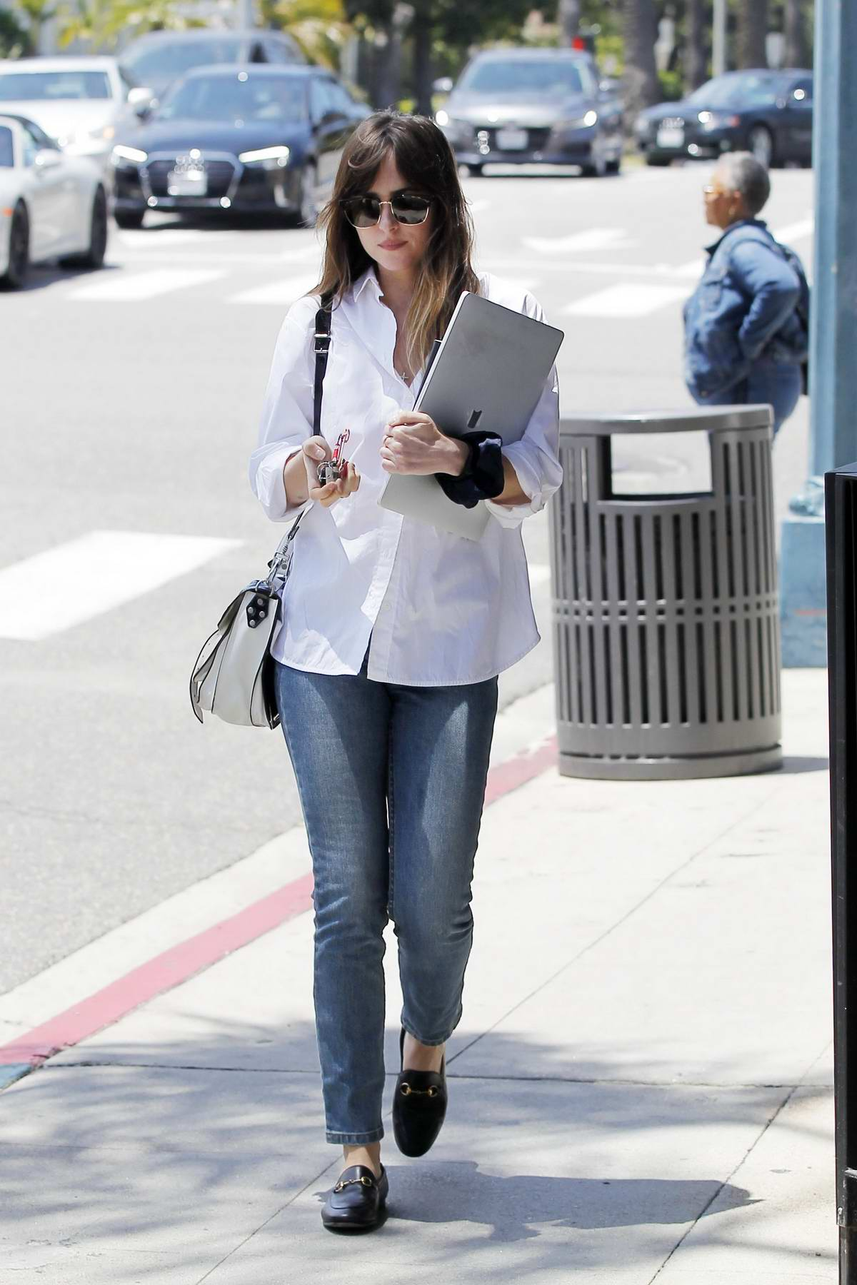 Dakota Johnson holds on to her MacBook as she leaves lunch wearing a white shirt and blue jeans in Beverly Hills, Los Angeles