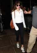 Dakota Johnson keeps it casual with a white sweatshirt and black leggings as she leaves The Mark in New York City