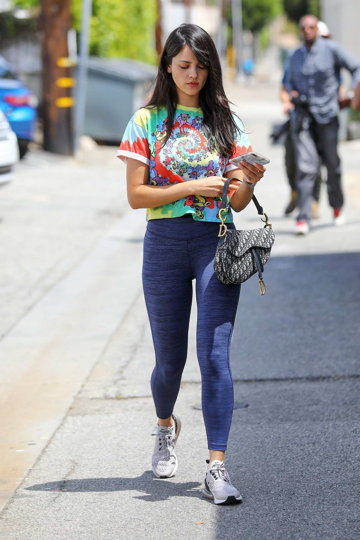 Eiza Gonzalez wears a colorful tie-dye top and blue leggings during a trip to the hair salon in Los Angeles