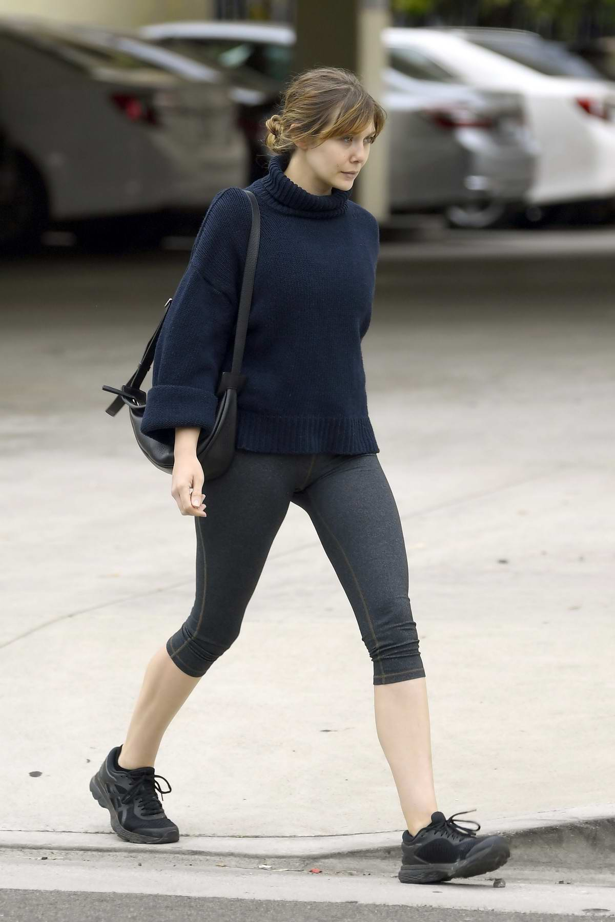 Elizabeth Olsen wears a navy blue turtleneck sweater and grey leggings as she leaves the gym in Los Angeles