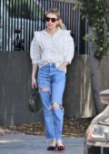 Emma Roberts wears a ruffled white shirt and ripped jeans while out to lunch with a friend at Little Dom's in Los Feliz, California
