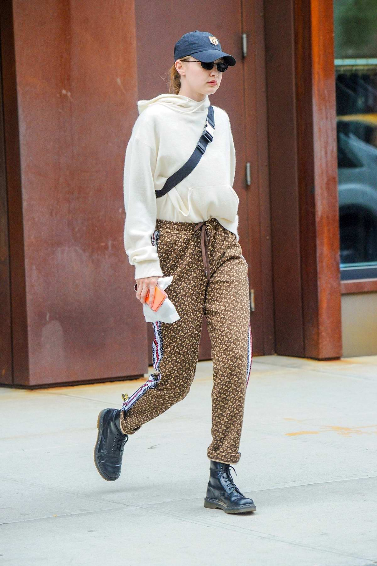 Gigi Hadid looks stylish in a Burberry pants paired with Doc Marten boots and a Prada side bag as she heads out in New York City