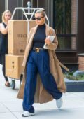 Hailey Baldwin Bieber looks chic in a camel trench coat over a black crop top and wide leg jeans as she heads out in New York City