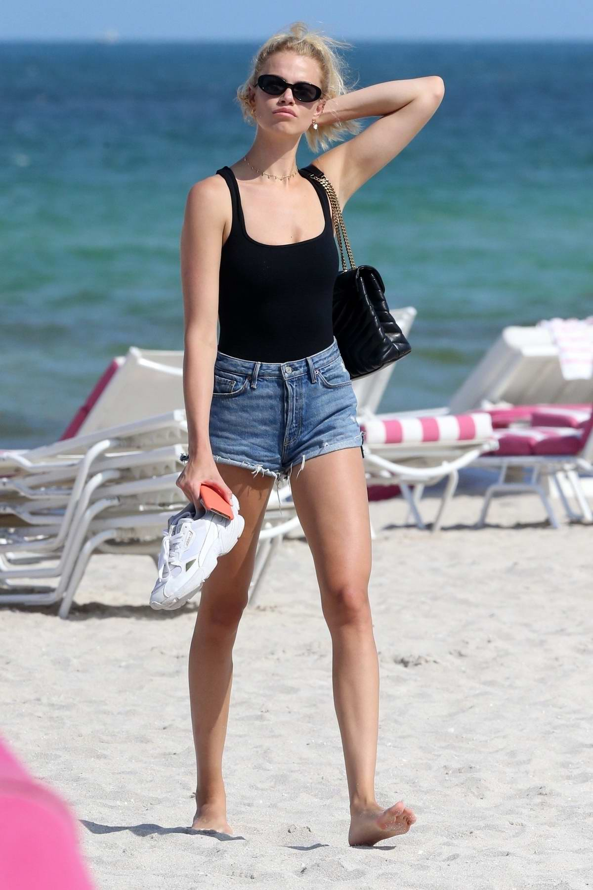 Hailey Clauson wears a black swimsuit as she hits the beach in Miami, Florida