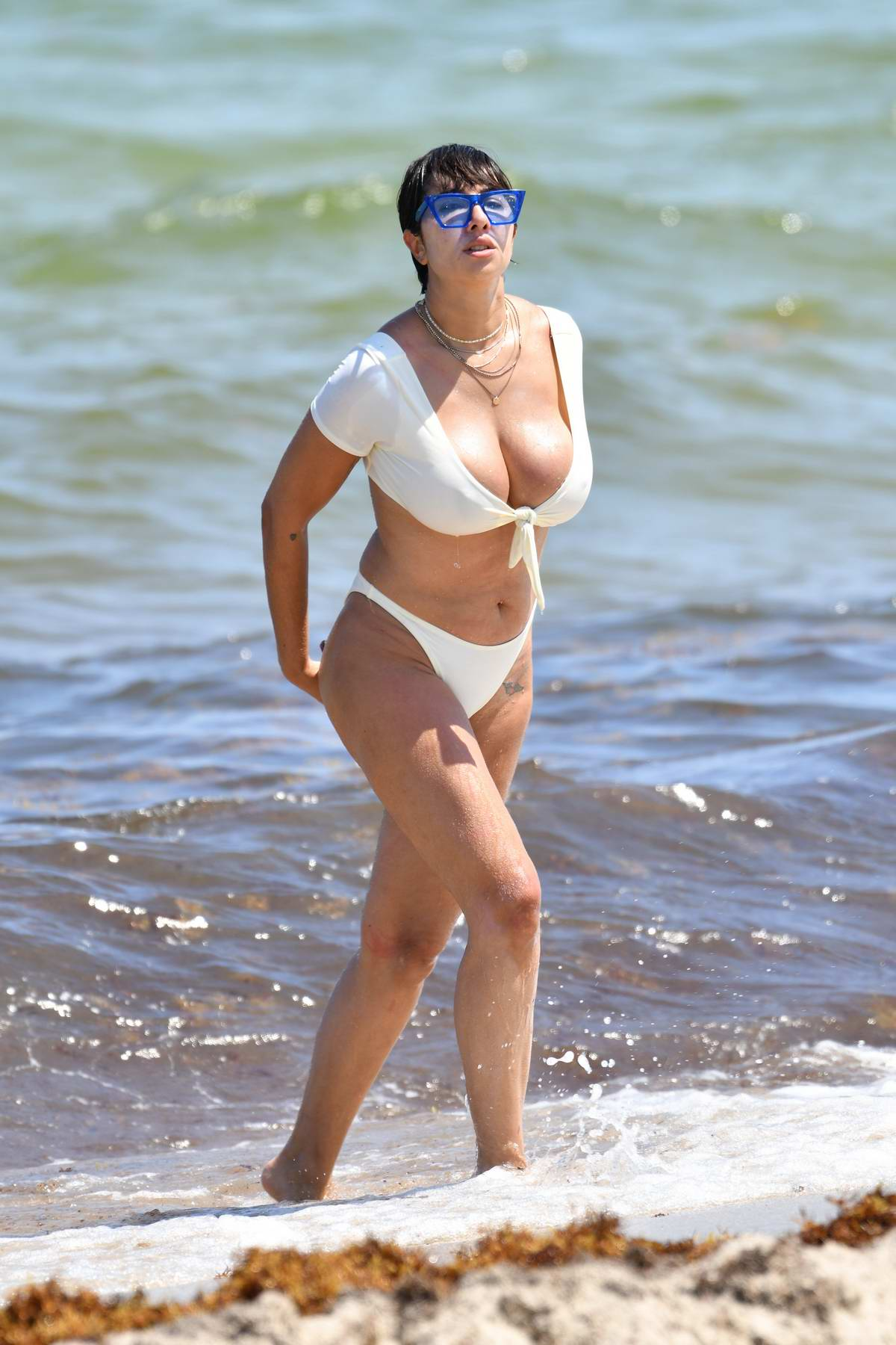 Jackie Cruz wears a tie front white bikini as she relaxes and hits the water on Miami Beach, Florida