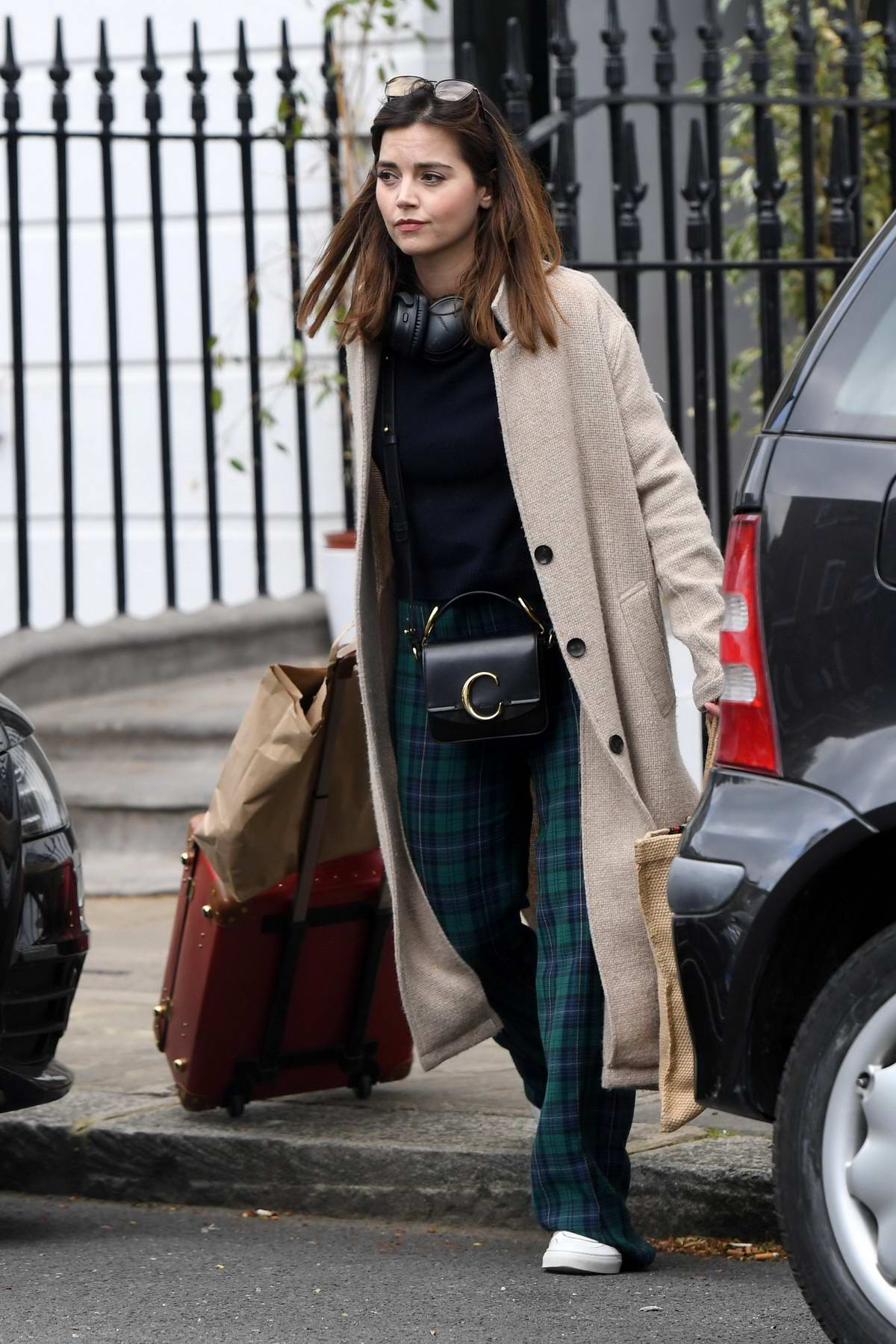 Jenna Coleman looks lovely in a beige long coat with tartan plaid trousers as she heads out in London, UK