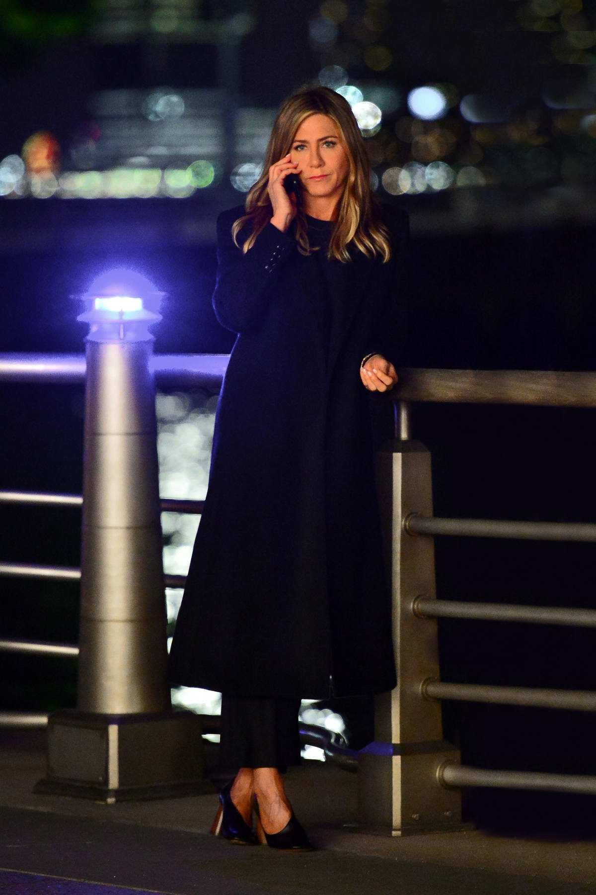 Jennifer Aniston dressed in all black while filming a late night scene for an upcoming project in New York City