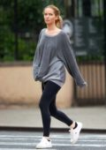 Jennifer Lawrence wears a grey sweatshirt and black leggings as she steps out for a stroll in light drizzle in New York City