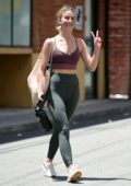 Julianne Hough flashes the peace sign as she leaves after a workout in a purple sports bra and green leggings in Studio City, Los Angeles