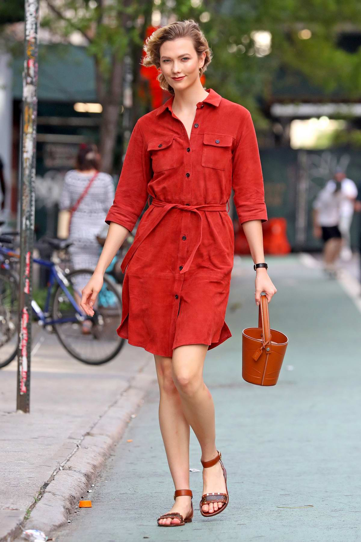Karlie Kloss looks striking in a red button up dress and mini bucket bag in New York City