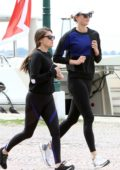 Karlie Kloss wears a blue and black sweatshirt with black leggings while out for a run in Venice, Italy