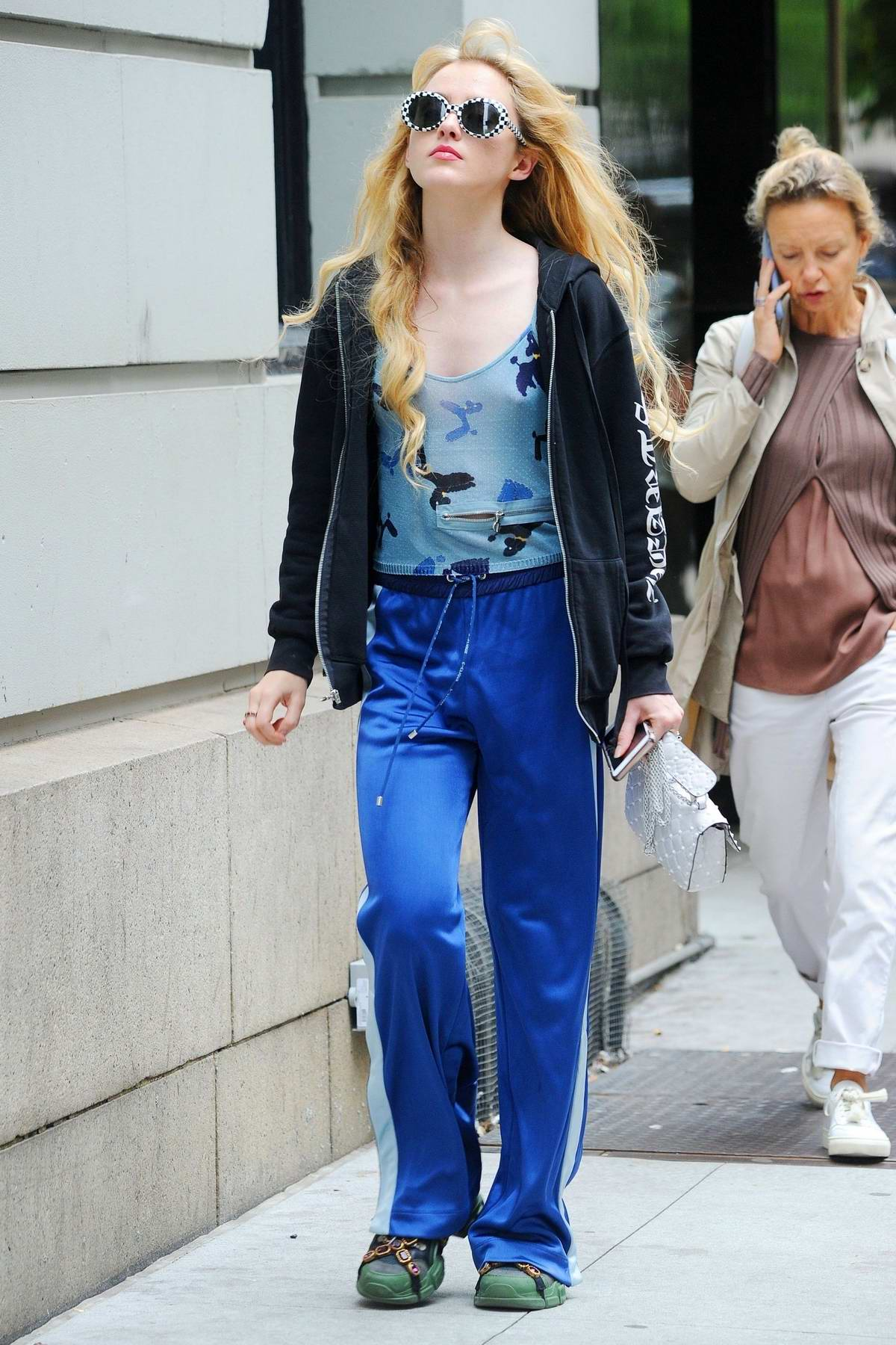 Kathryn Newton rocks a pair of cool checkered sunglasses and Gucci sneakers while out with a friend in New York City
