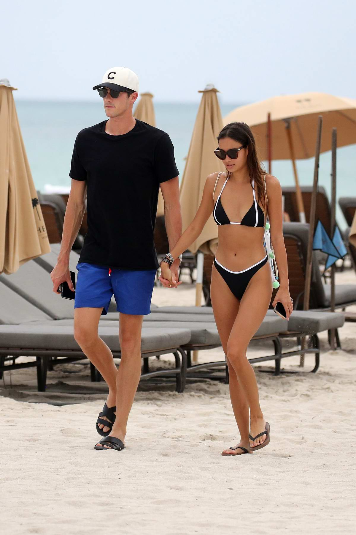 Kelsey Merritt and Conor Dwyer show off their beach bodies as they hit the waves in Miami, Florida