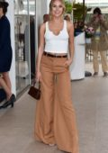 Kimberley Garner wears a white tank top and brown wide-leg pants as she arrives at the Martinez hotel in Cannes, France