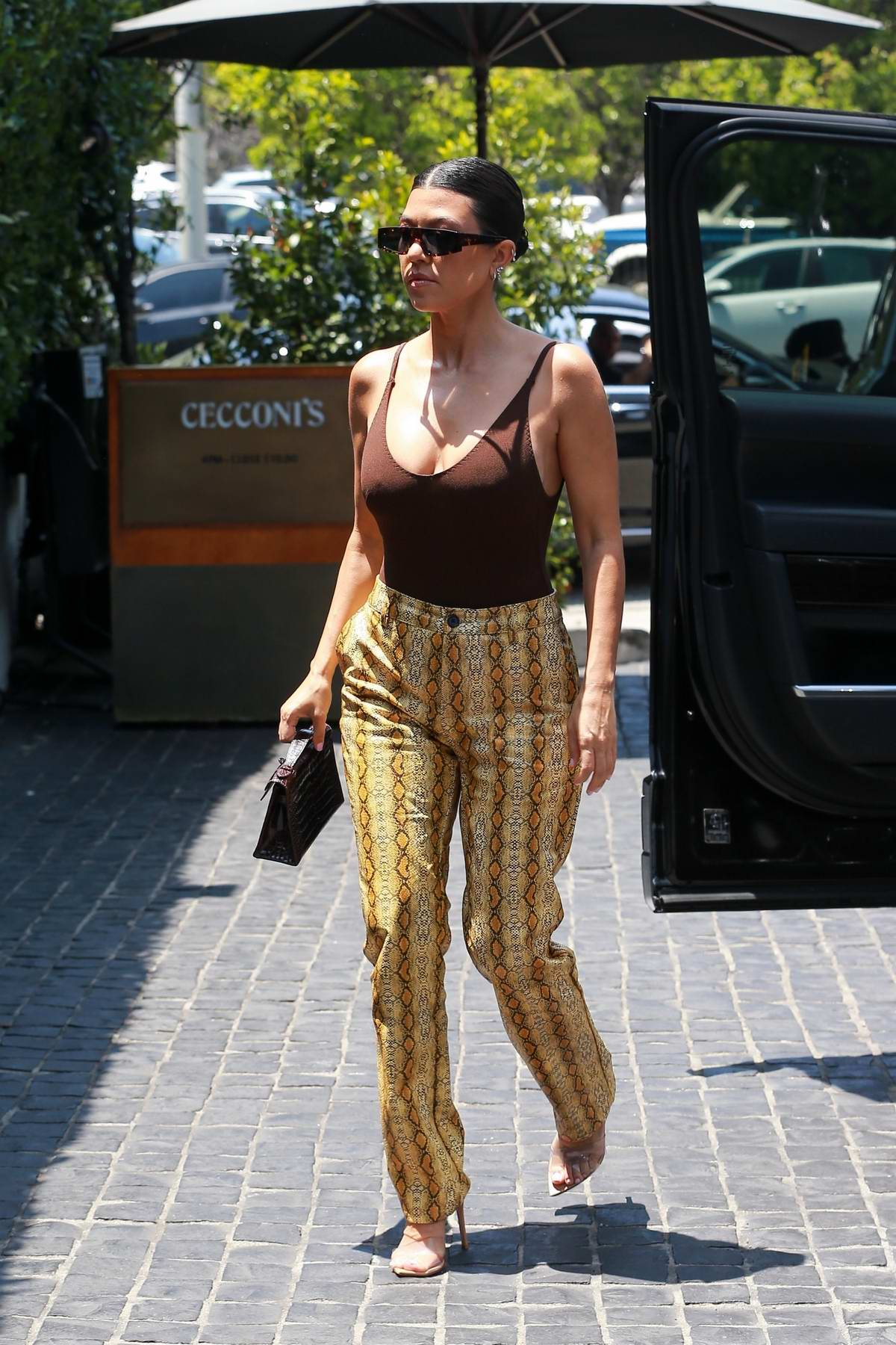 Kourtney Kardashian rocks a brown tank top and snakeskin print pants as she arrives at Cecconi's for lunch in Los Angeles