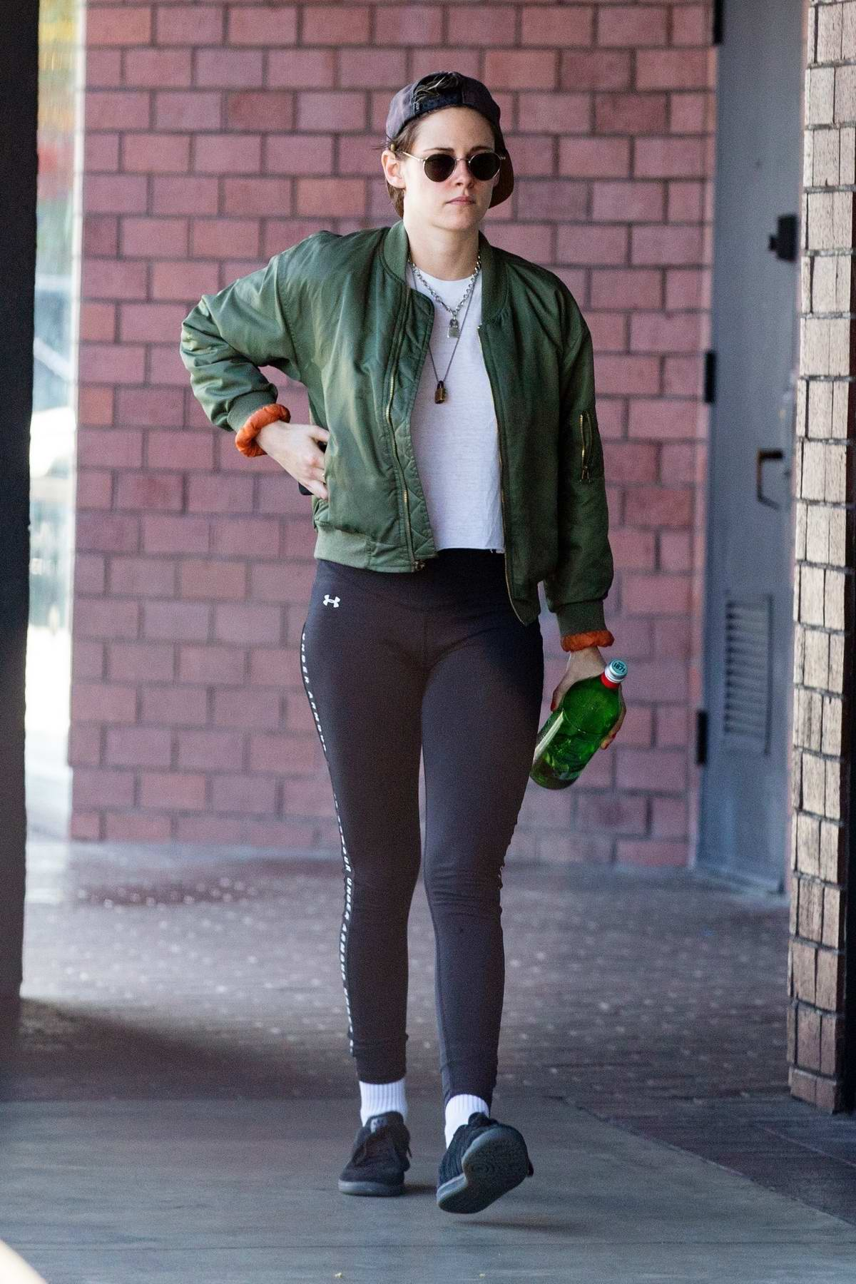 Kristen Stewart sports a green jacket with black Under Armour leggings as she leaves a health spa in Hollywood, California