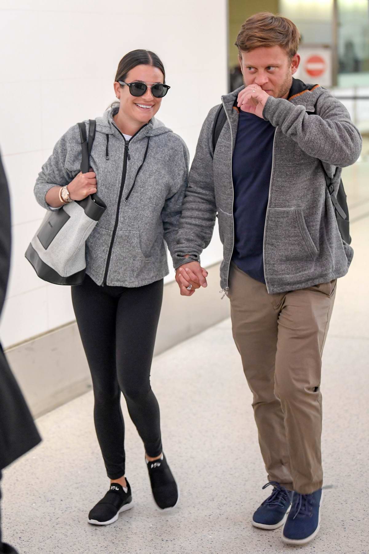 Lea Michele and Zandy Reich hold hands as they touch down in Los Angeles