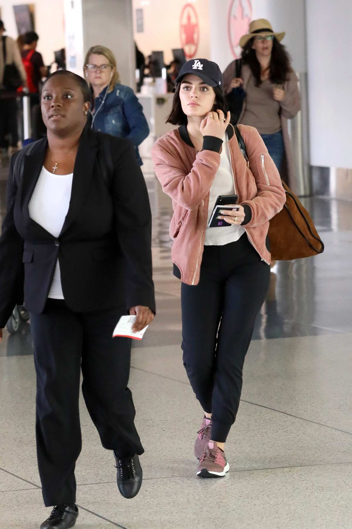 Lucy Hale dons a peach colored jacket with 'LA' hat as she arrives at LAX in Los Angeles