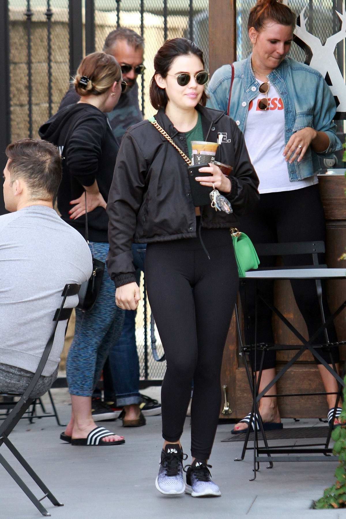 Lucy Hale rocks black jacket, green top and black leggings while out to pickup a couple of iced coffee from Alfred's in Los Angeles