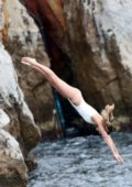 Margot Robbie takes a dive into the pool in a white swimsuit at Eden Roc Hotel in Antibes, France