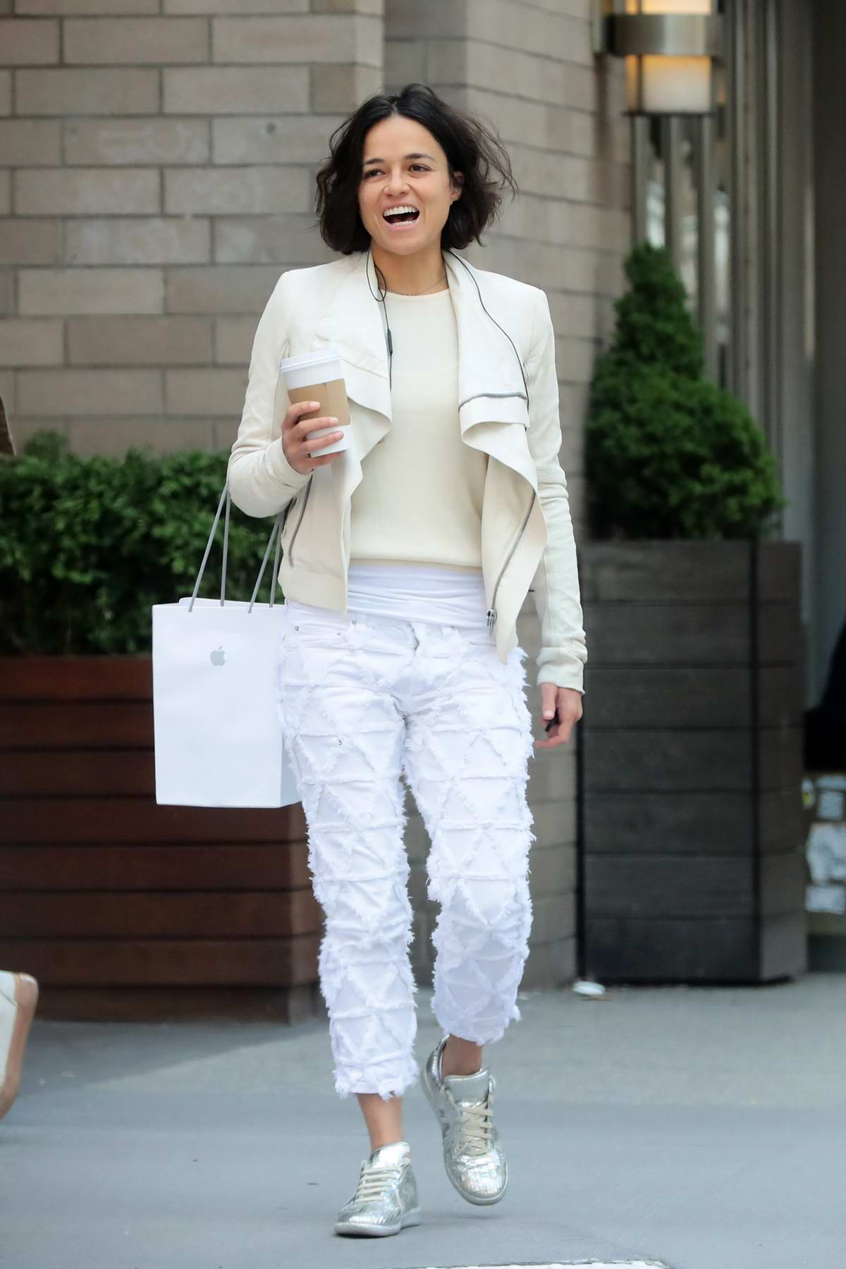 Michelle Rodriguez enjoys a cup of coffee after shopping at an Apple store in New York City