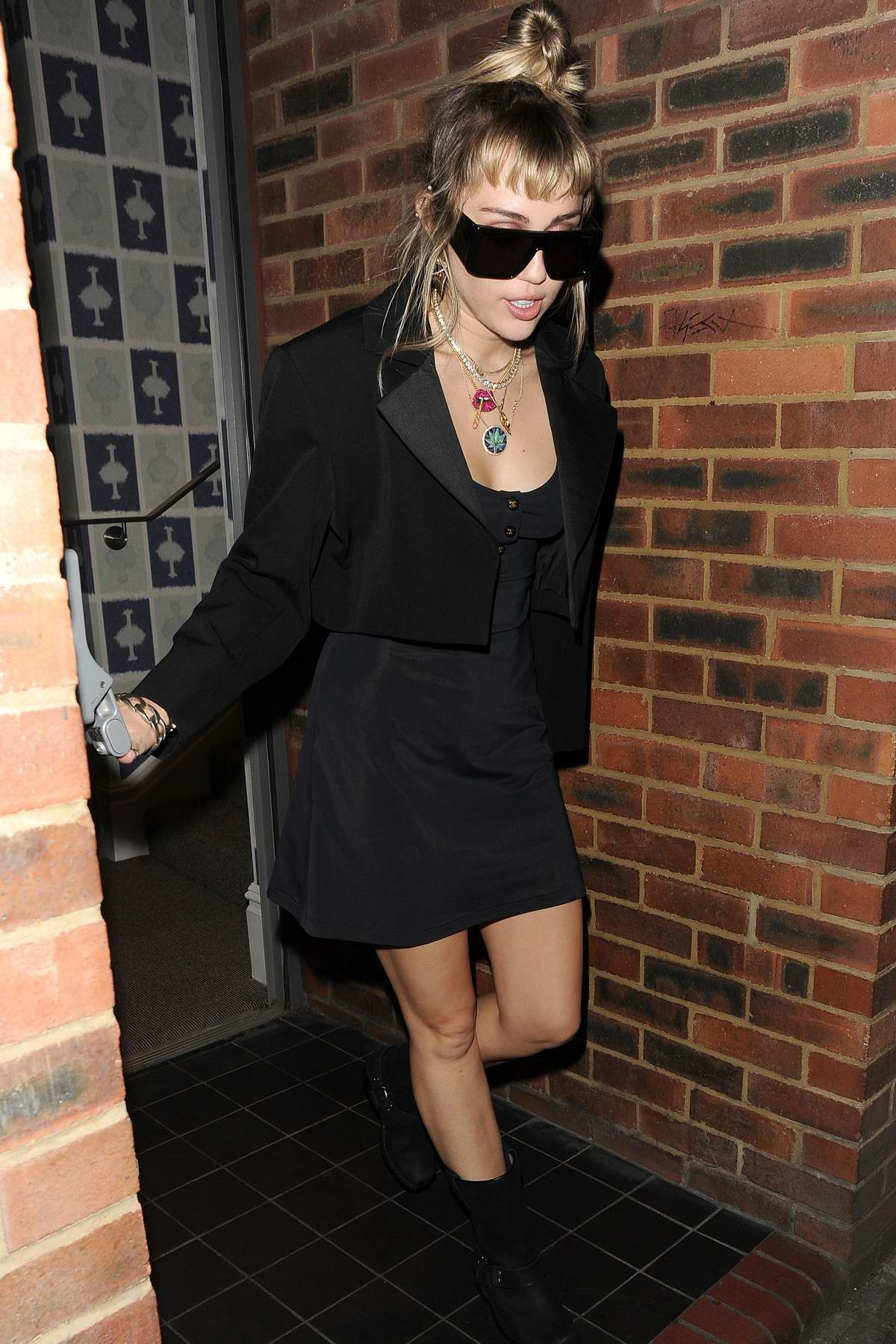 Miley Cyrus rocks a pair of cool shades with an all-black ensemble as she leaves the Soho Hotel in London, UK