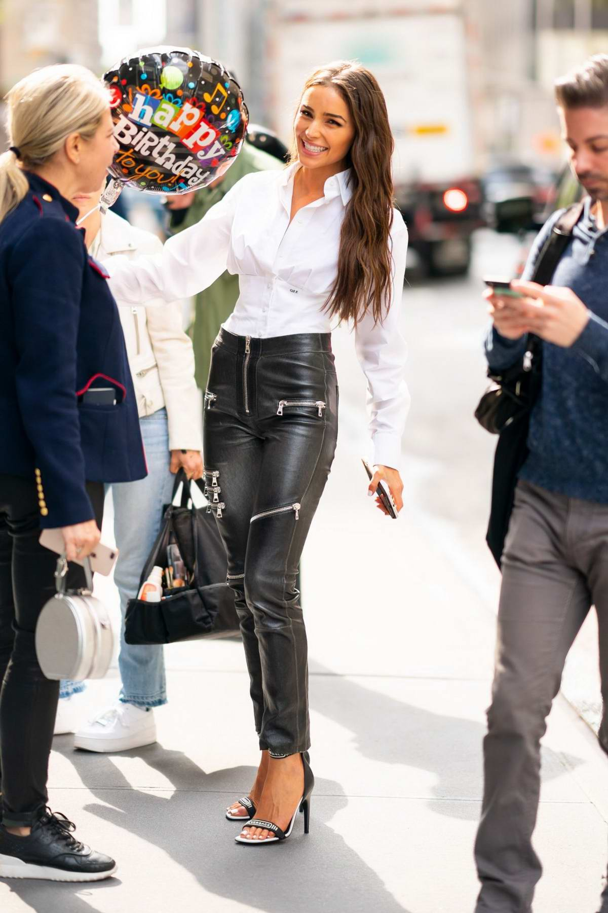 Olivia Culpo looks dapper in a white shirt and black leather pants as she steps out on her birthday in Midtown, New York City