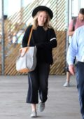 Olivia Wilde is all smiles as she arrives at JFK Airport in New York City