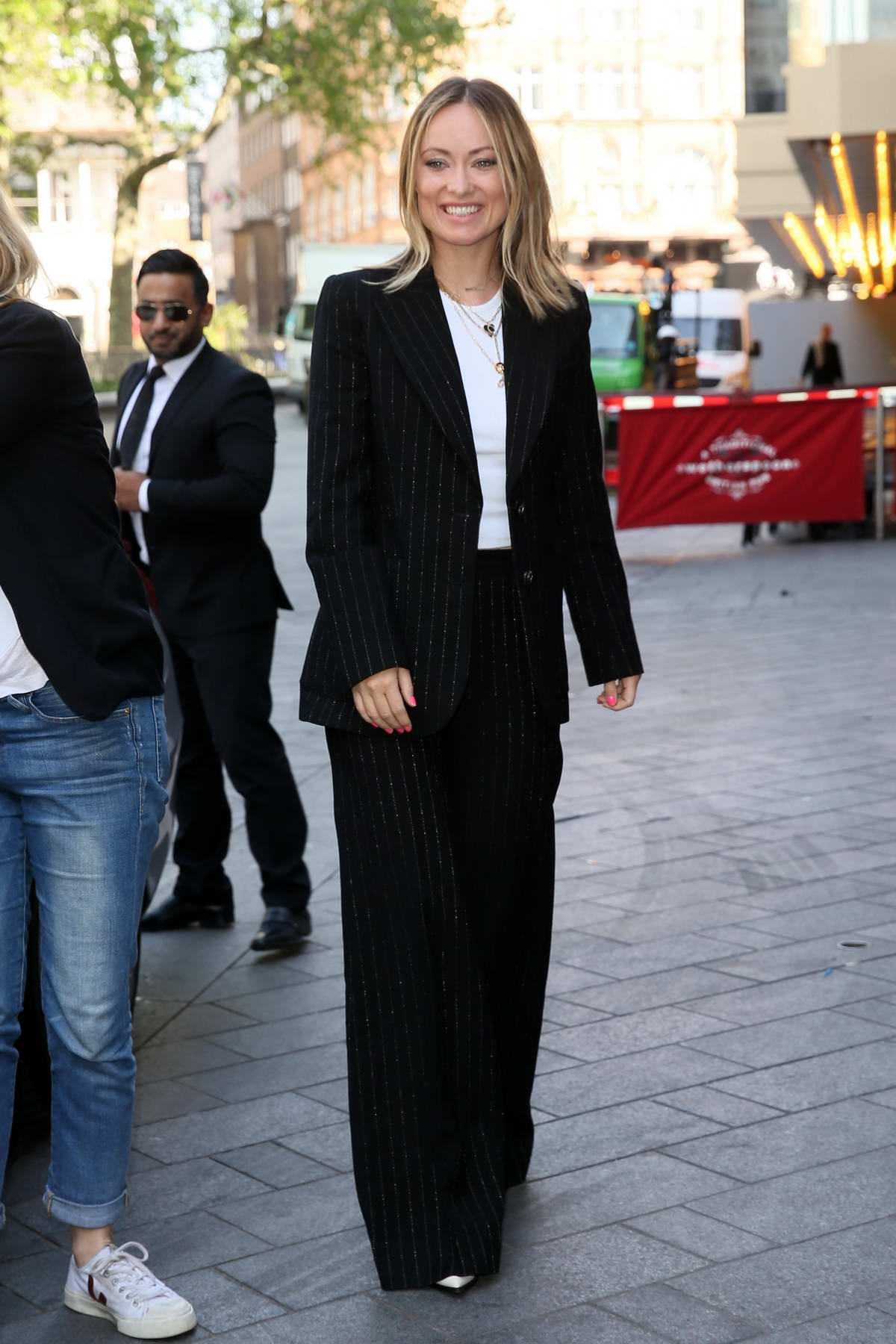 Olivia Wilde wears a black pinstriped suit as she arrives at Global studios in London, UK