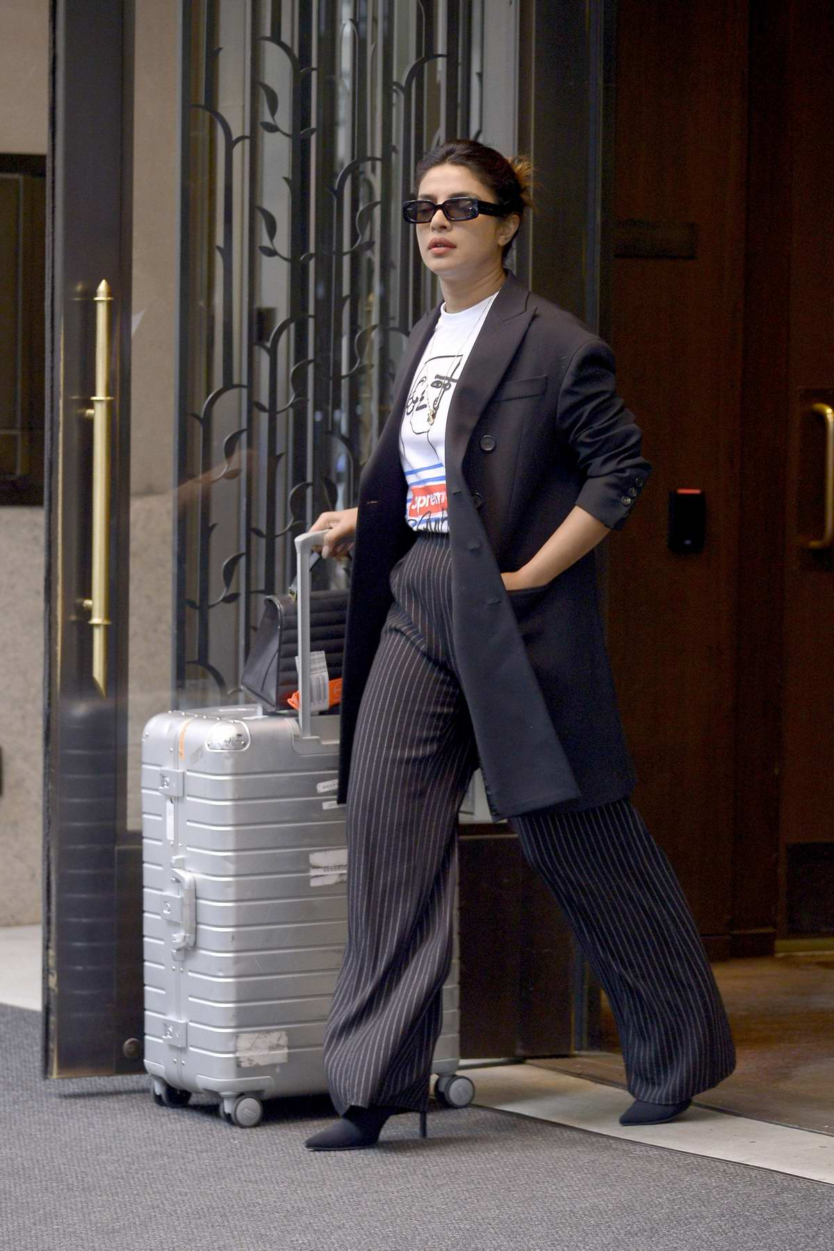 Priyanka Chopra spotted in a black blazer with pinstriped trousers as she heads out with a suitcase New York City