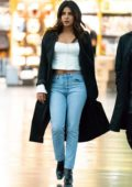 Priyanka Chopra wears a crop white blouse with a long trench coat as she arrives at the JFK airport in New York City
